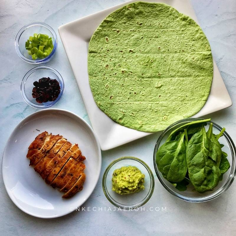 Ingredients for making this recipe includes green spinach wrap, sautéed chicken breast, guacamole, fresh spinach, dry cranberries and green onions