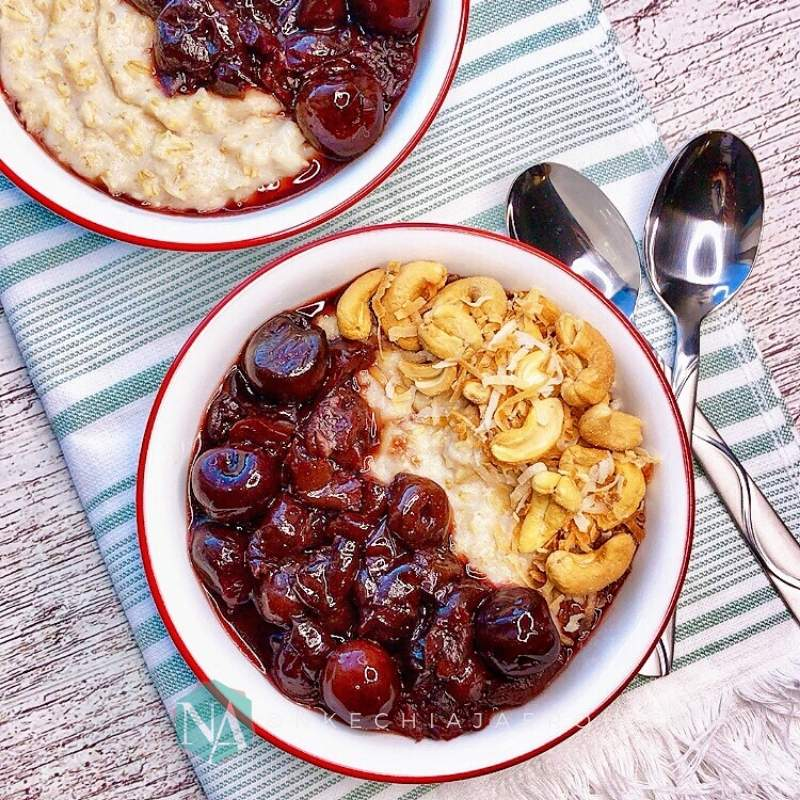 Comforting coconut milk oatmeal porridge with stewed cherry topping