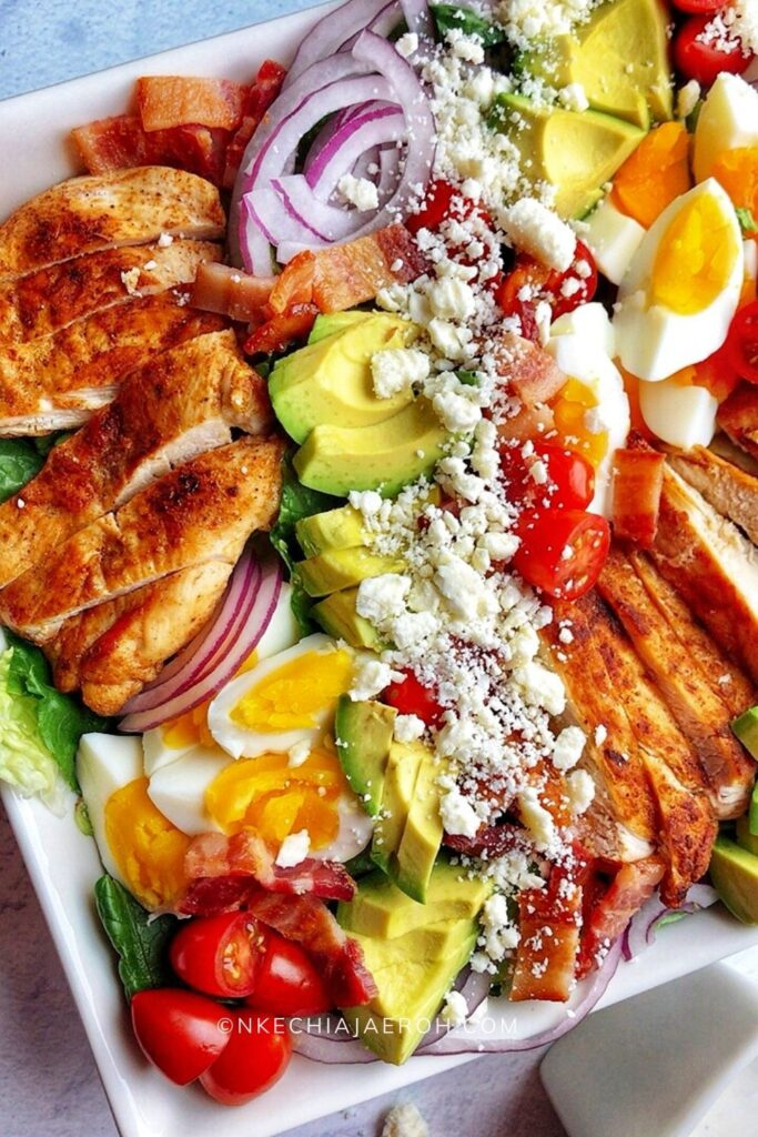 Healthy and delicious keto cobb salad is low-calorie (low-carb, obviously), gluten-free, very tasty, and full of flavors. This salad is made with fresh romaine lettuce, sautéed chicken breast, crispy bacon, hard-boiled eggs, cherry tomatoes, avocado, and crumbled feta cheese. The best thing about this cobb salad is it can be prepped ahead, which means it comes together quickly whenever you want to eat it! This is the low-carb meal prep salad recipe you are looking for; easy, breezy, and tasty! Definitely a must-try! #Cobbsalad #Ketorecipe #ketocobbsalad #healthysalad #lowcarbsalad