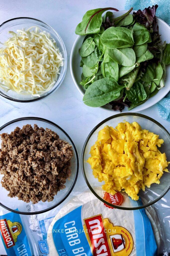 Healthy freezer breakfast burritos ingredients - scrambled eggs, turkey sausage, leafy greens, and low-carb tortillas