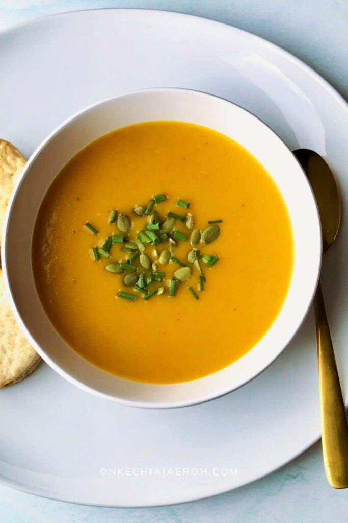 Easy autumn squash soup Panera copycat is rich, nutritious, comforting, and delicious! This healthy butternut squash soup recipe is sweet, savory, and creamy. This soup is vegan, gluten-free, refined sugar-free, and stress-free. A perfect Panera copycat autumn squash soup loaded with butternut squash, celery, ginger, onions, pumpkin puree, coconut milk, vegetable broth, and more! #Butternutsquashsoup #Butternutsquash #soup #Panerasquashsoup #Autumnsquashsoup #fall #winter #glutenfree #vegan