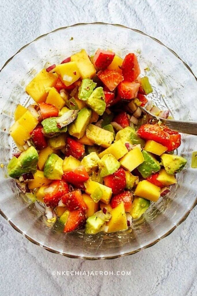 Easy and most delightful mango strawberry avocado salad is fresh, flavorful, bright, crisp, and sweet! This salad is loaded with a combination of fruits and vegetables in season during the summer. A fruity salad you can serve with meat or fish for a more filling meal or use as salsa. Equally, this is one fresh and flavorful salad that you can load up on salad greens. Did I hear you say perfection? Yes, indeed! #Mangosalad #mangosalsa #Strawberrysalad #AvocadoSalsa #easysalad #summertime #summersalad #20minutemeal #fruitsalad